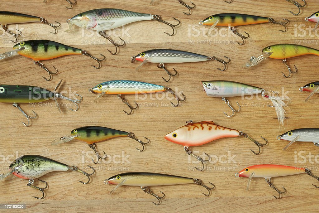 Group of colorful fishing lures with hooks on wood background stock photo