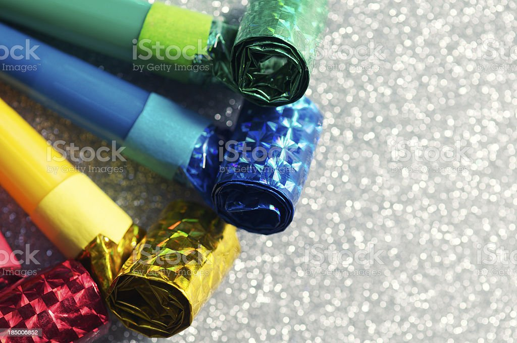 Group of Colorful Party Horn Blowers Sparkly Silver Background stock photo