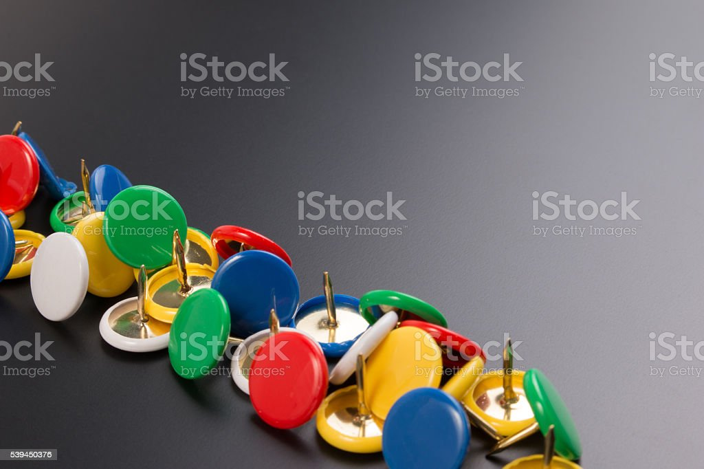 Group of colorful push pins on black board background. stock photo