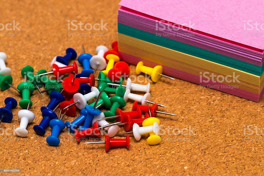 Group of colorful push pins on cork board stock photo