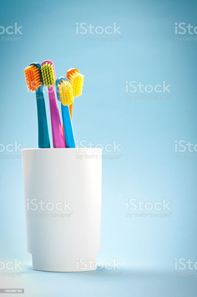 Group of colourful soft toothbrushes in white mug on blue stock photo