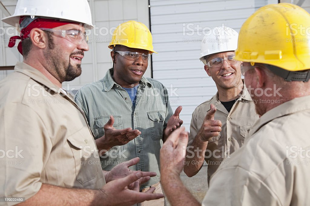 Group of construction workers talking stock photo