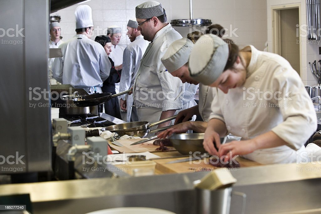 Group of cooks working in a industrial kitchen royalty-free stock photo