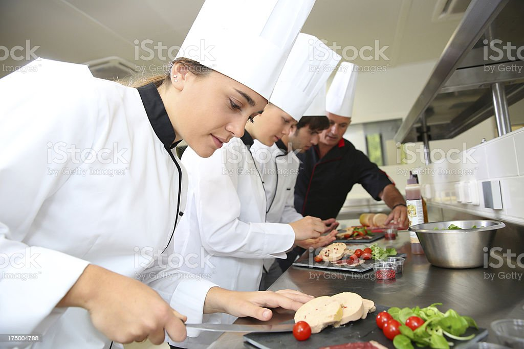 Group of cooks working with chef in kitchen stock photo