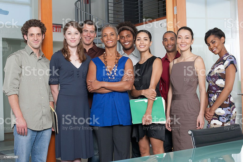 Group of coworkers in an office smiling stock photo
