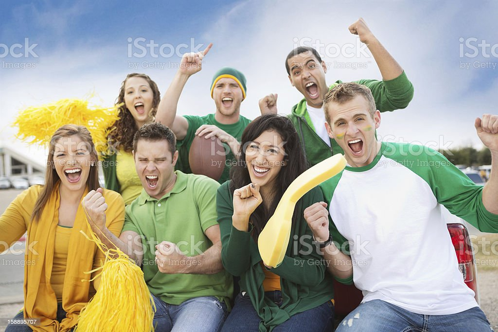 Group of crazy fans tailgating at football game near stadium stock photo