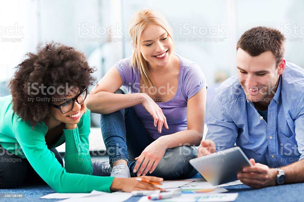 Group of creative professionals working on floor stock photo