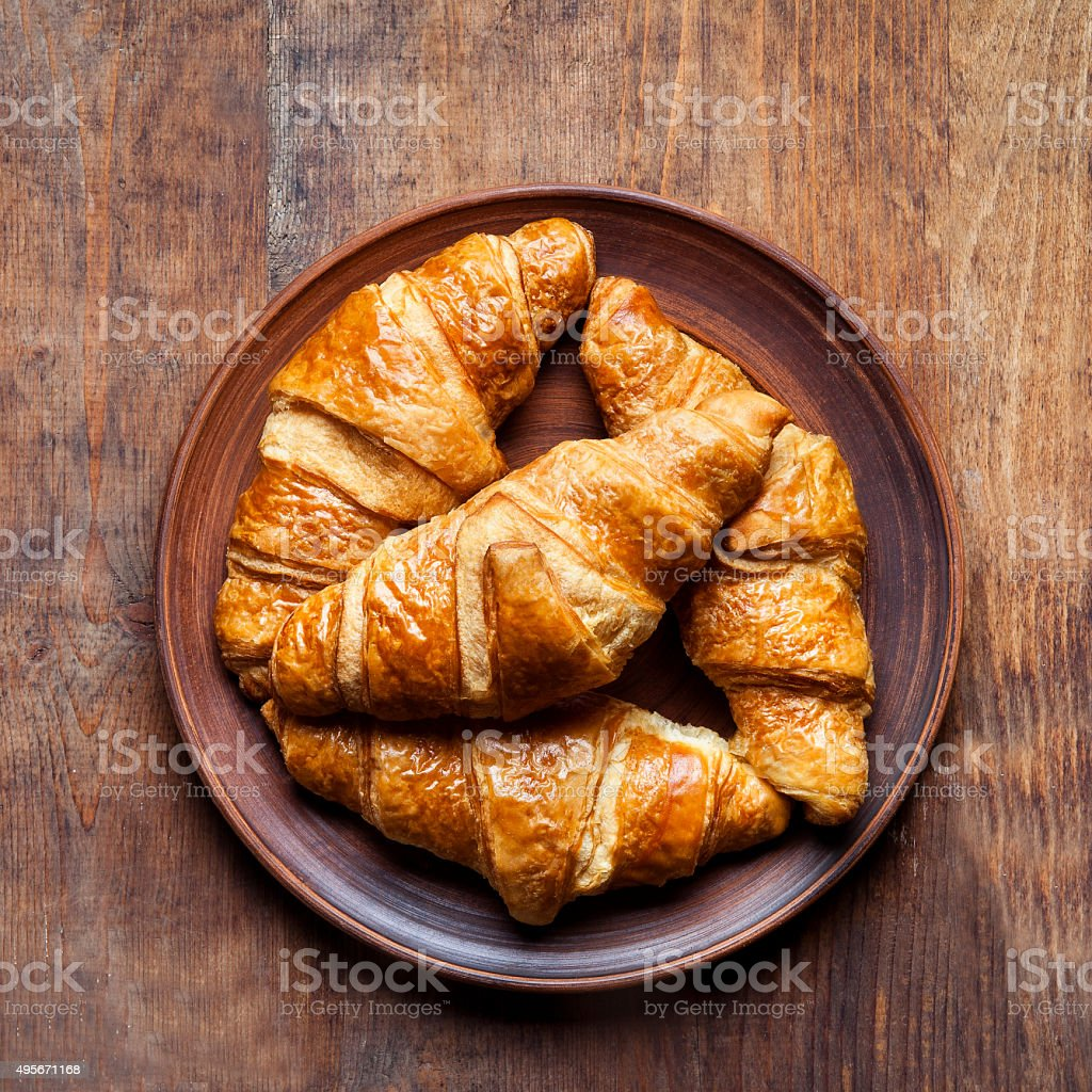 group of Croissants on a plate on a wooden table. stock photo
