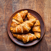 group of Croissants on a plate on a wooden table.