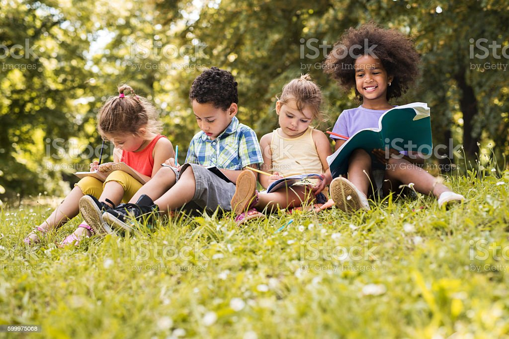 Group of cute kids writing in notebooks at the park. stock photo