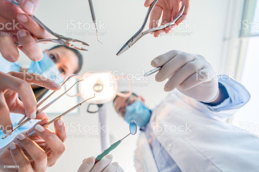 Group of dental surgeons holding tools stock photo