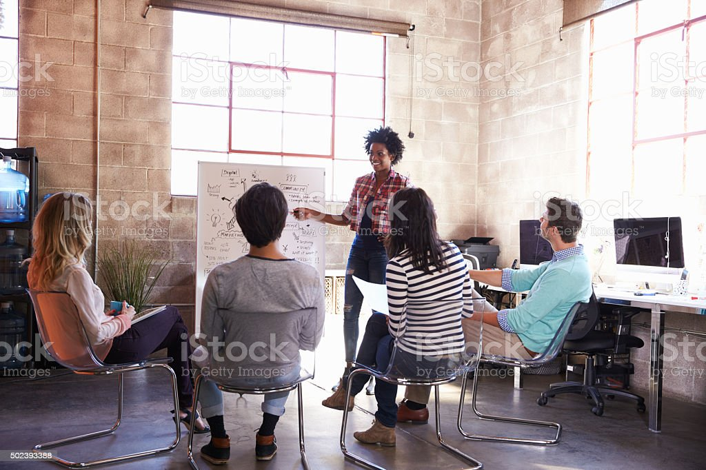 Group Of Designers Having Brainstorming Session In Office stock photo
