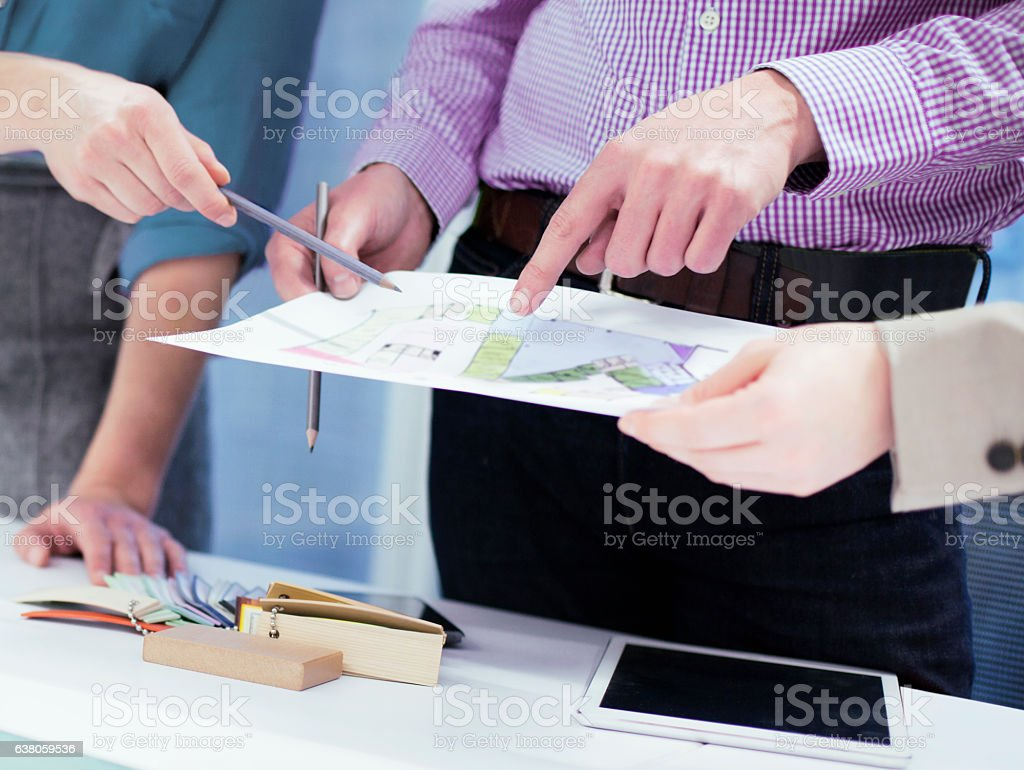 Group of designers pointing to architectural layout diagram stock photo