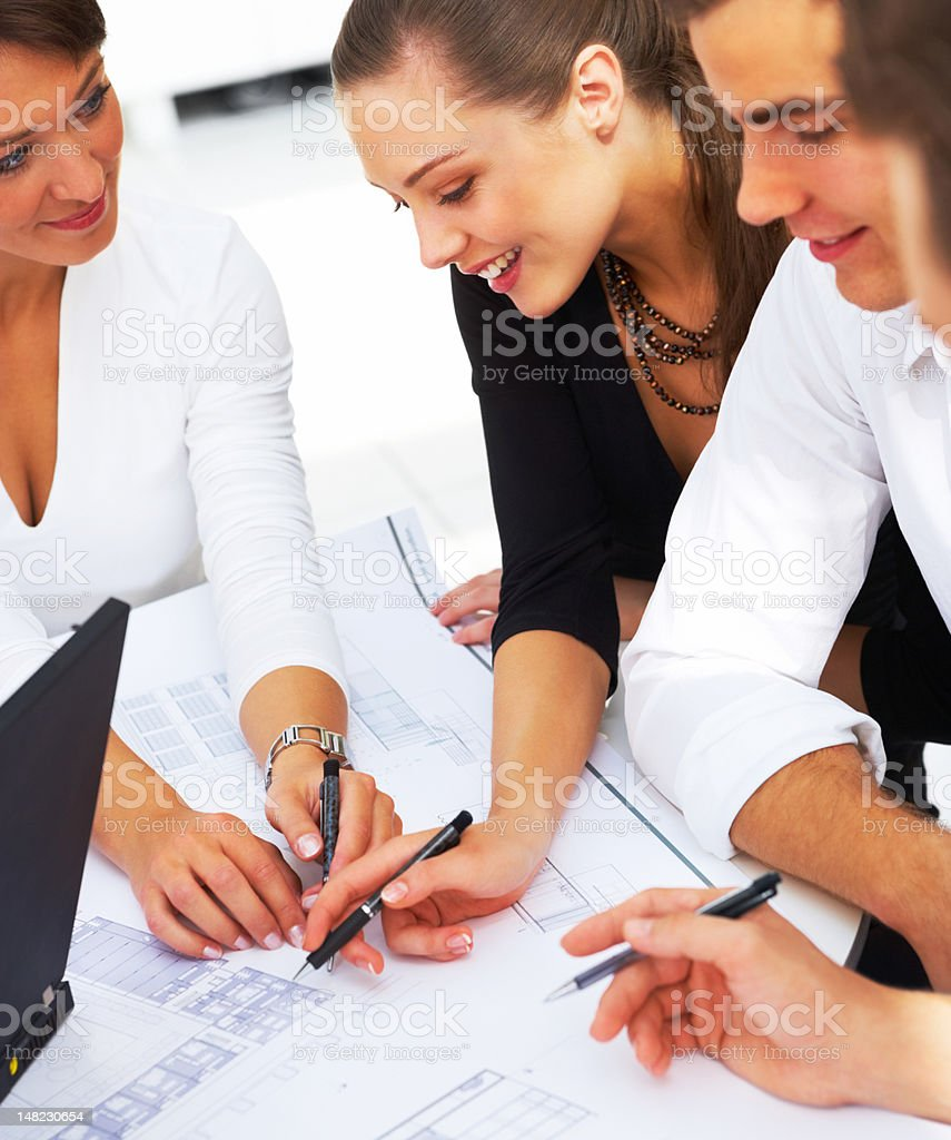 Group of designers working on blueprint royalty-free stock photo
