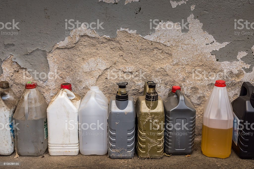group of dirty plastic containers in front of a wall. stock photo