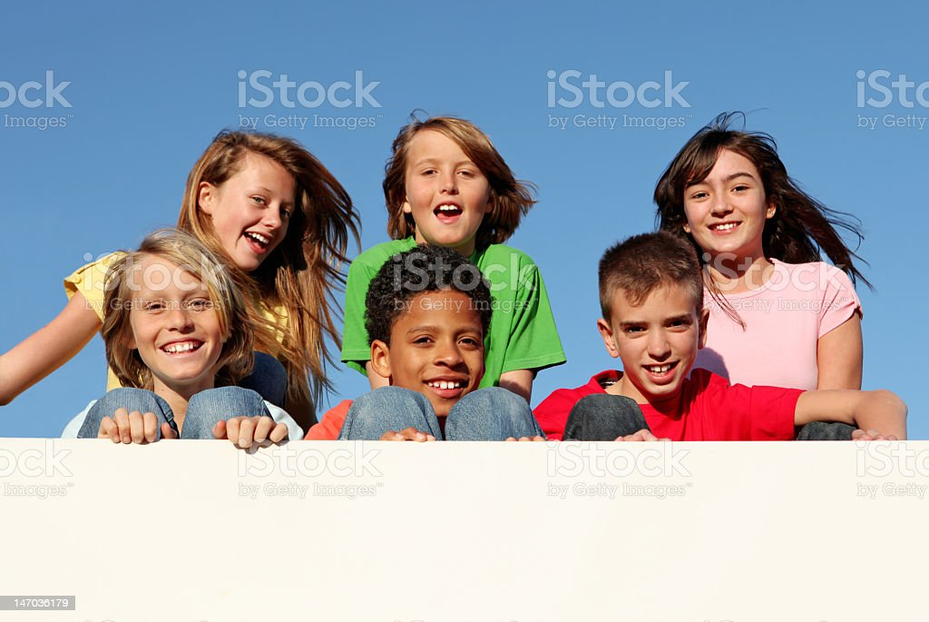 Group of diverse children holding a blank sign stock photo