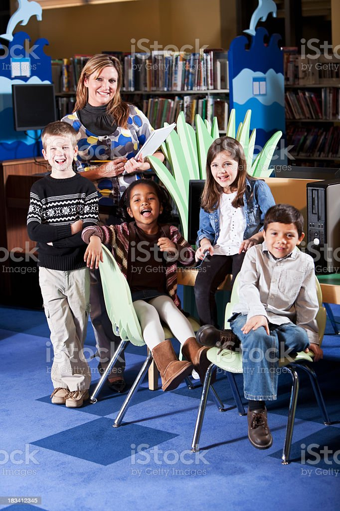 Group of diverse children in the library with librarian stock photo