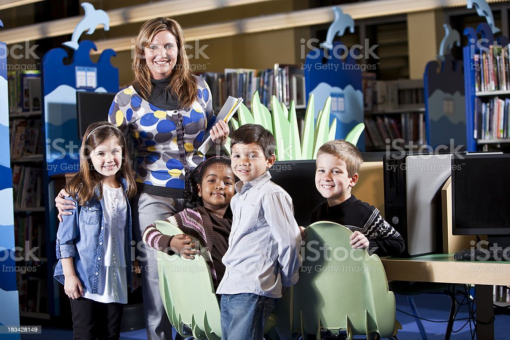 Group of diverse children in the library with teacher stock photo