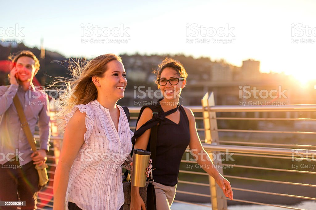 Group of diverse female professionals chatting while walking to work stock photo