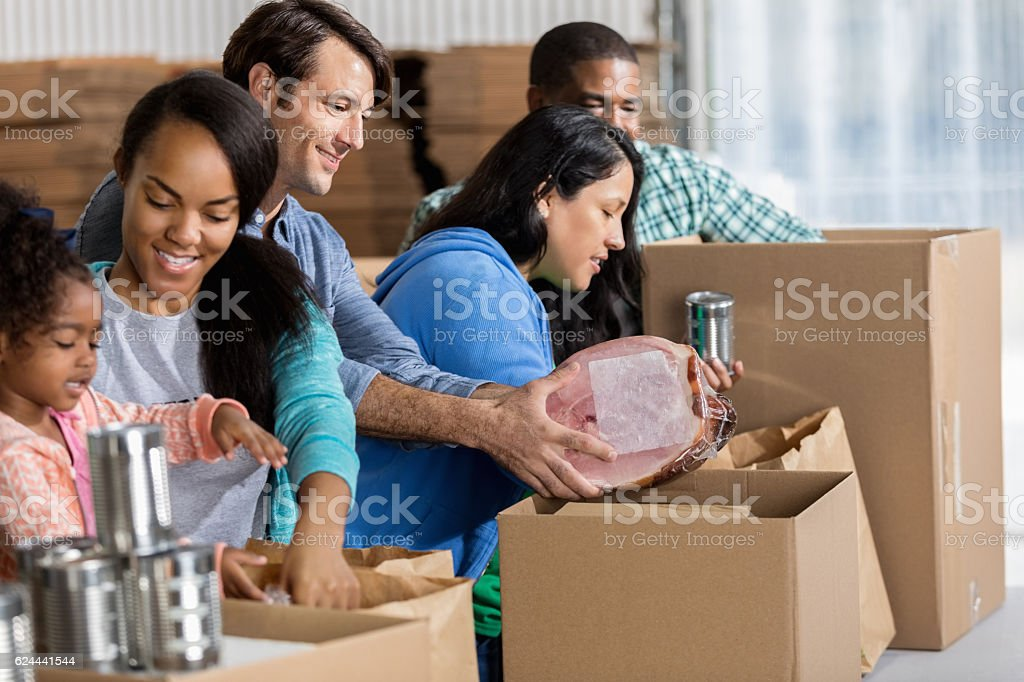 A group of divers volunteers work together during a food drive in...