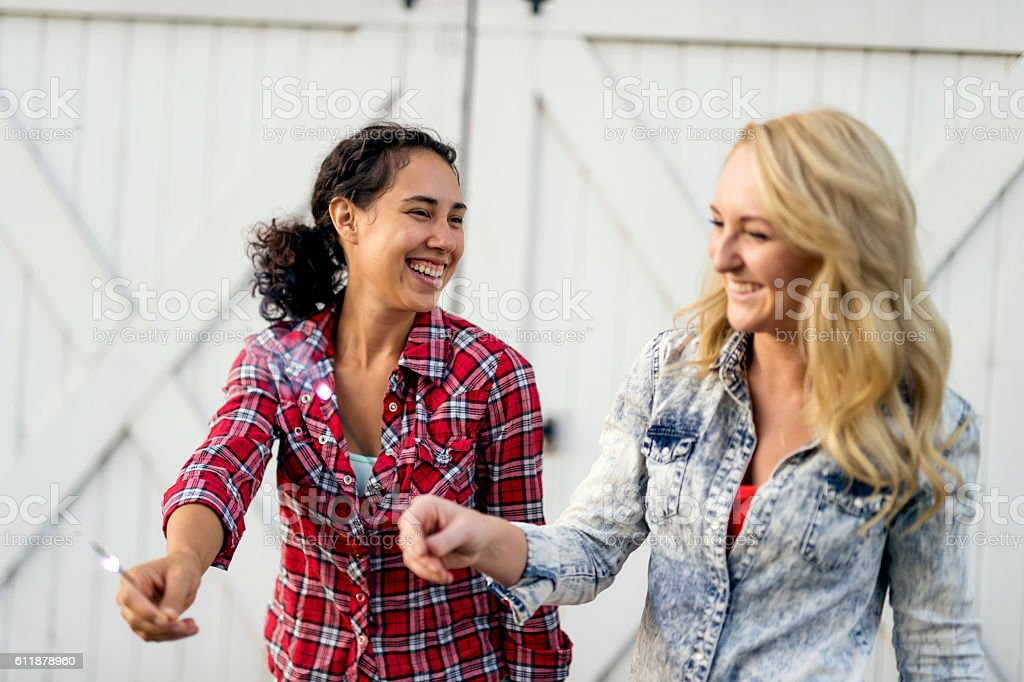 Group of diverse young adult friend holding sparklers stock photo