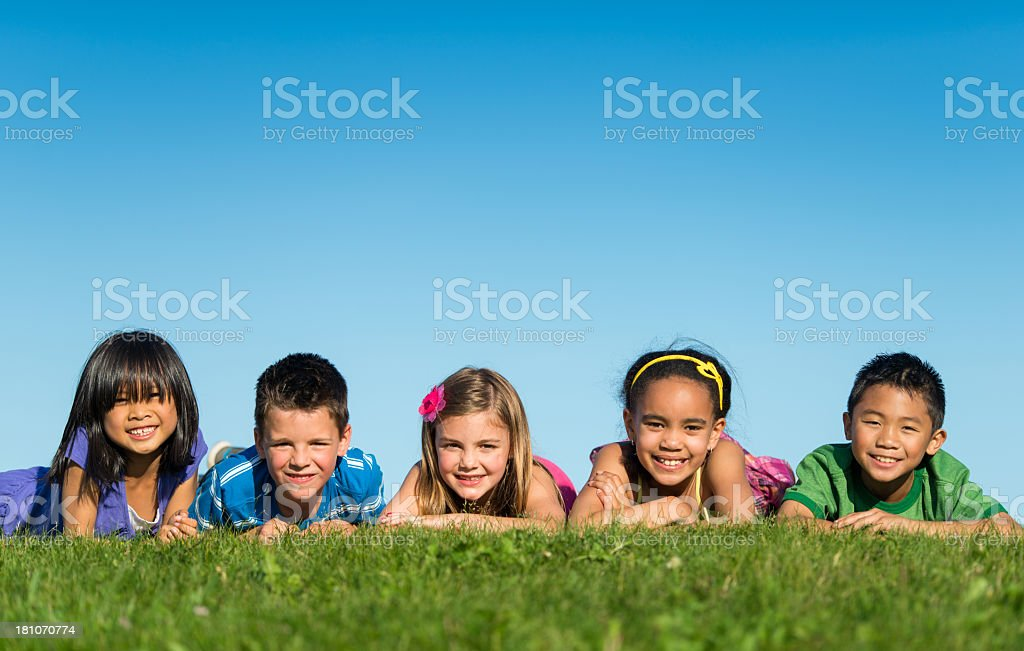 Group of diverse youngsters lying on the grass royalty-free stock photo