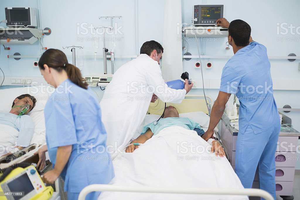 Group of doctor and nurses working with two patients stock photo