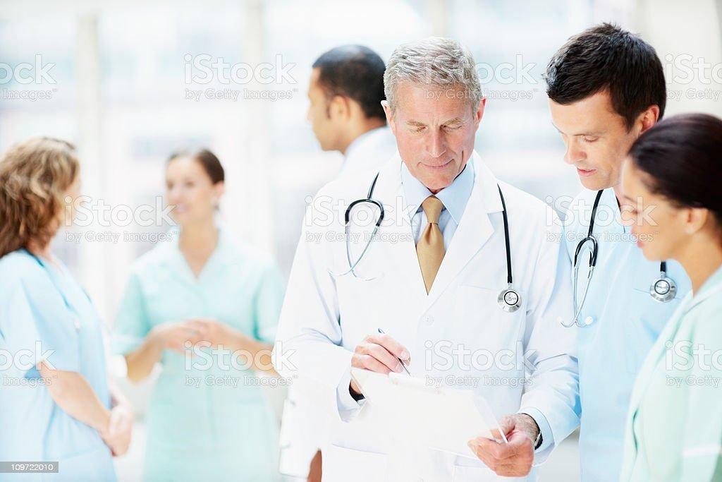 Group of doctors and nurses having a meeting against blur royalty-free stock photo