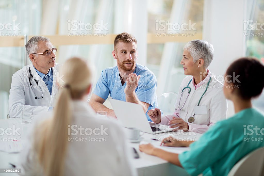 Group of doctors communicating on a meeting in the hospital. stock photo