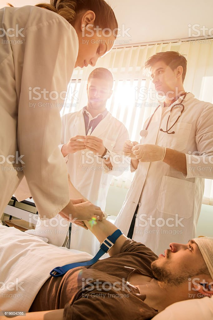 Group of doctors preparing patient for blood test in hospital. stock photo