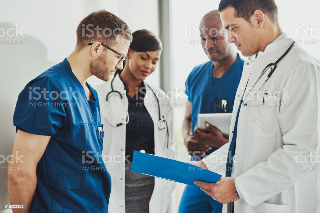 Group of doctors reading a document stock photo