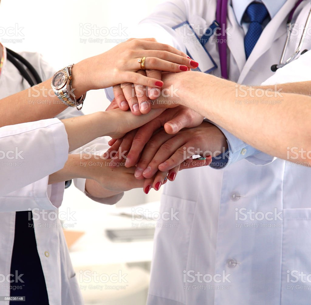 group of doctors shaking hands stock photo
