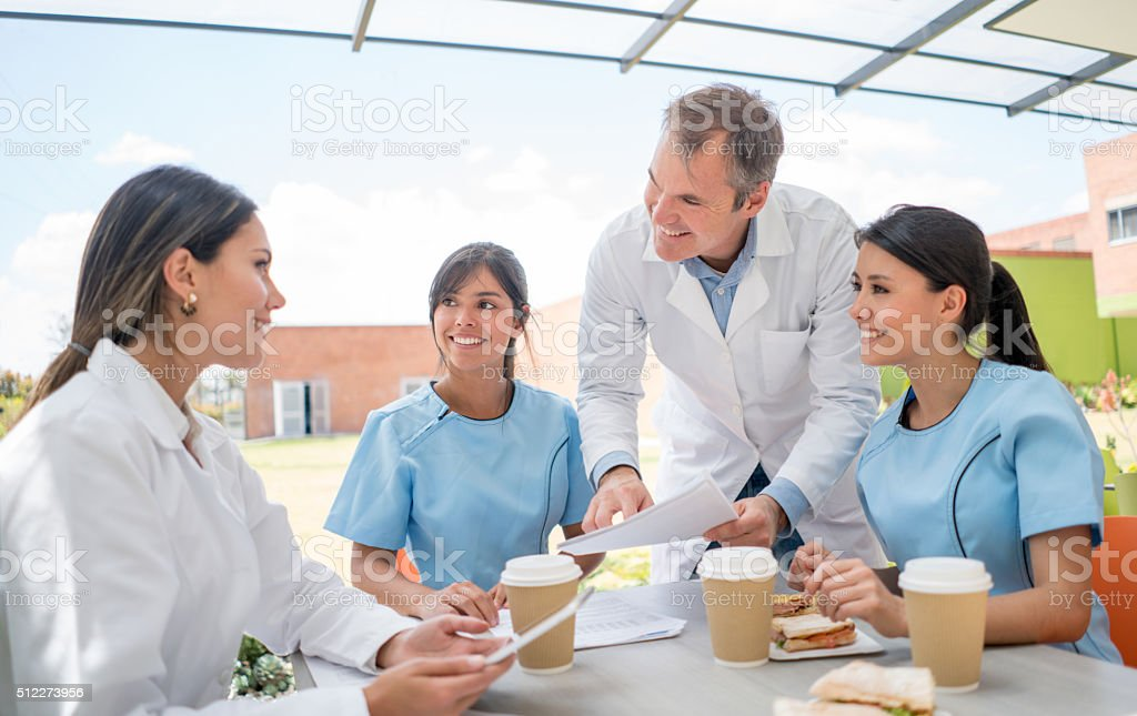 Group of doctors talking at the cafeteria stock photo
