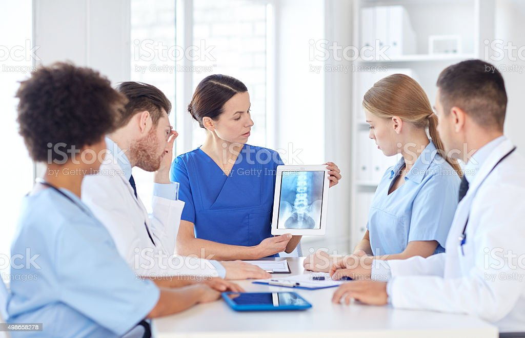 group of doctors with x-ray on tablet pc at clinic stock photo