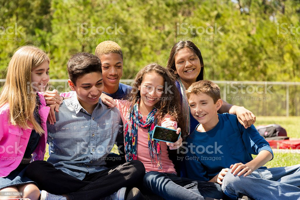 Group of early-teens friends take 'selfie' with smart phone. stock photo