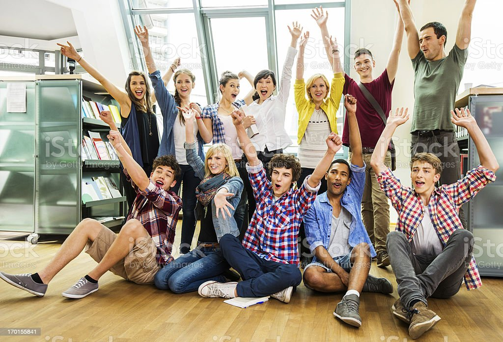 Group of ecstatic college students in the library. royalty-free stock photo