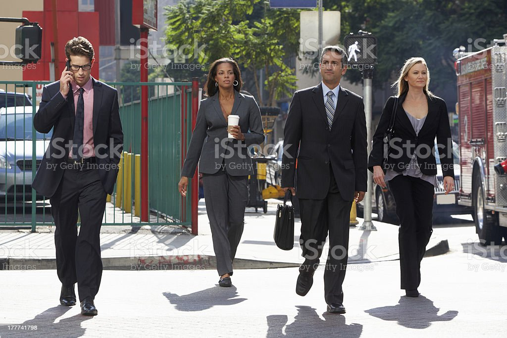 Group of elegant businesspeople crossing a street stock photo