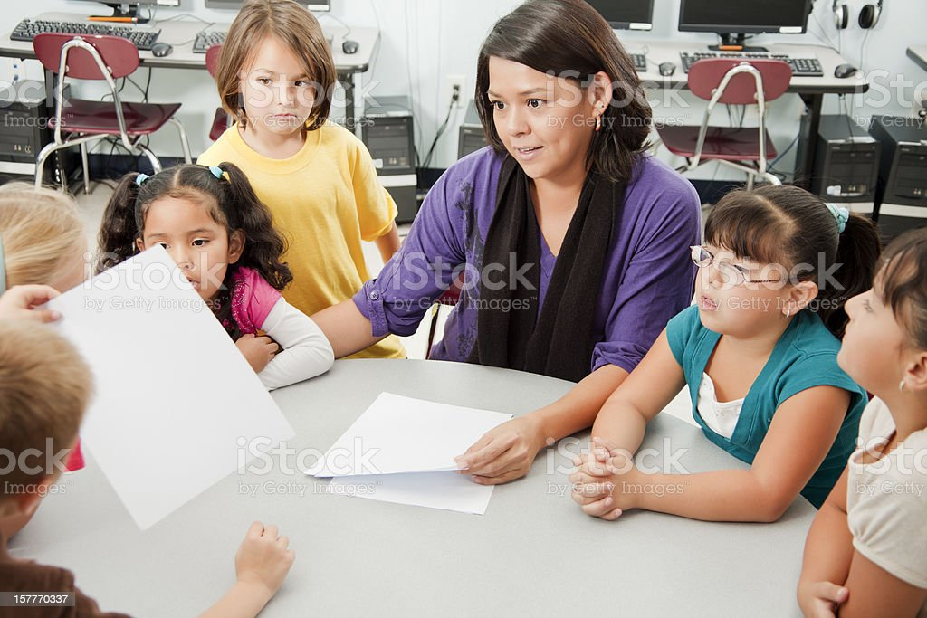 Group of elementary age children talking with their teacher royalty-free stock photo