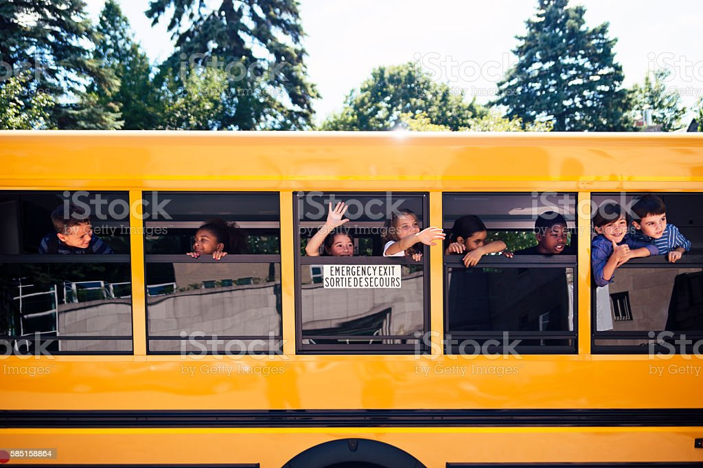 Group of elementary age kids on a yellow school bus. stock photo