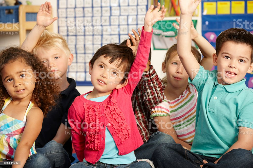 Group Of Elementary Age Schoolchildren Answering Question stock photo