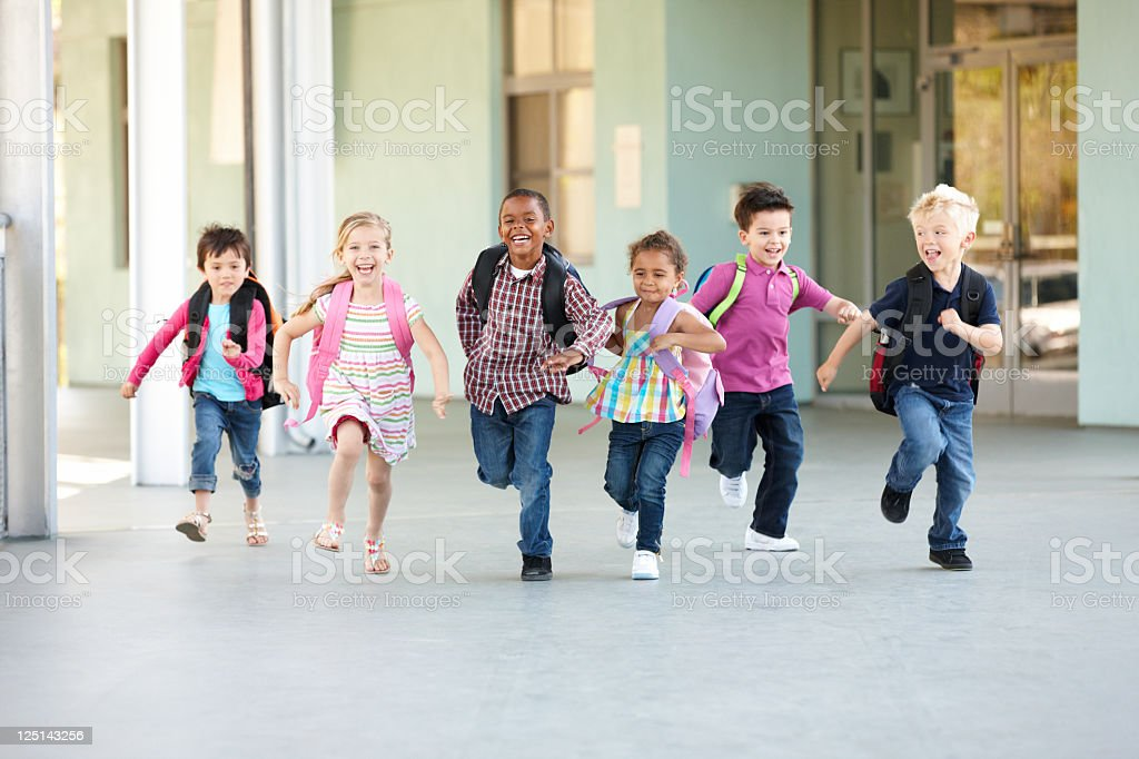 Group Of Elementary Age Schoolchildren Running Outside stock photo