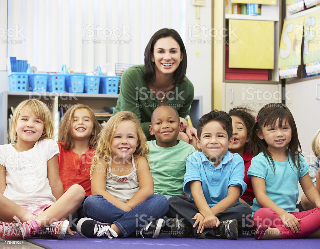 Group of Elementary Pupils In Classroom With Teacher stock photo