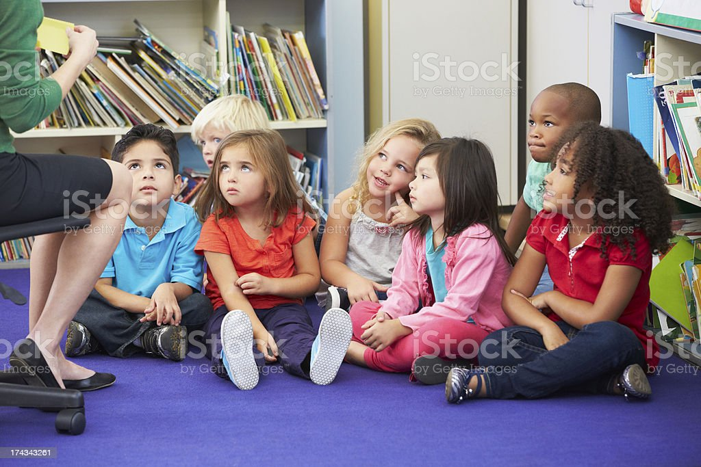 Group of Elementary Pupils In Classroom Working With Teacher stock photo