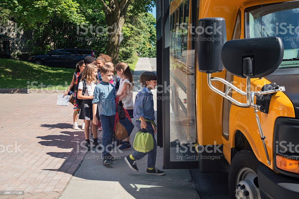 Group of elementary school kids getting in yellow school bus. stock photo