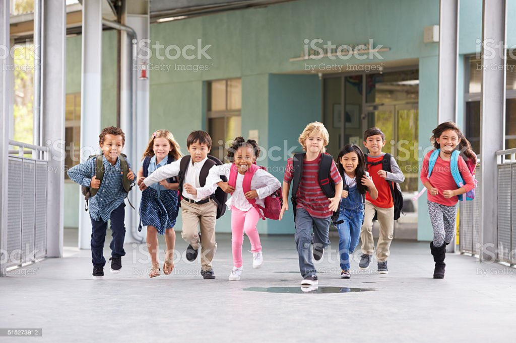 Group of elementary school kids running in a school corridor stock photo