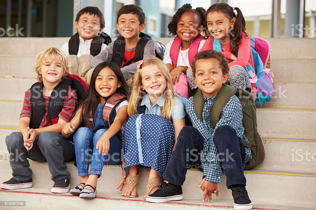 A group of elementary school kids sitting on school steps stock photo