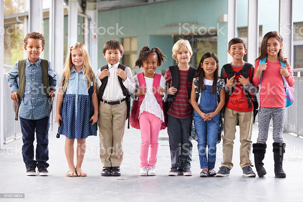 Group of elementary school kids standing in school corridor stock photo