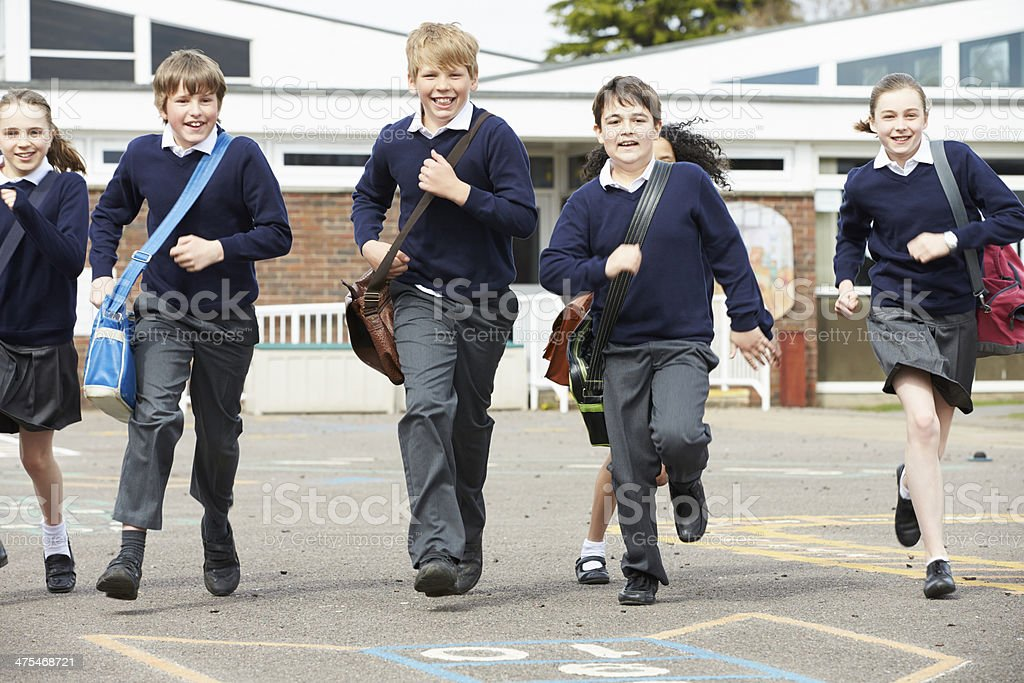 Group Of Elementary School Pupils Running In Playground stock photo