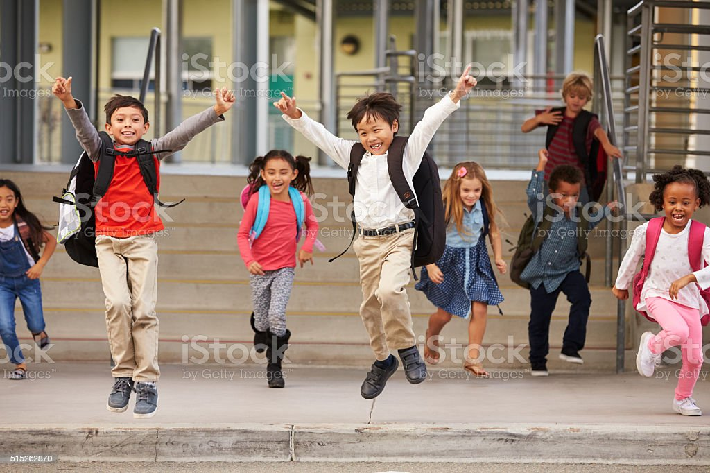 A group of energetic elementary school kids leaving school stock photo