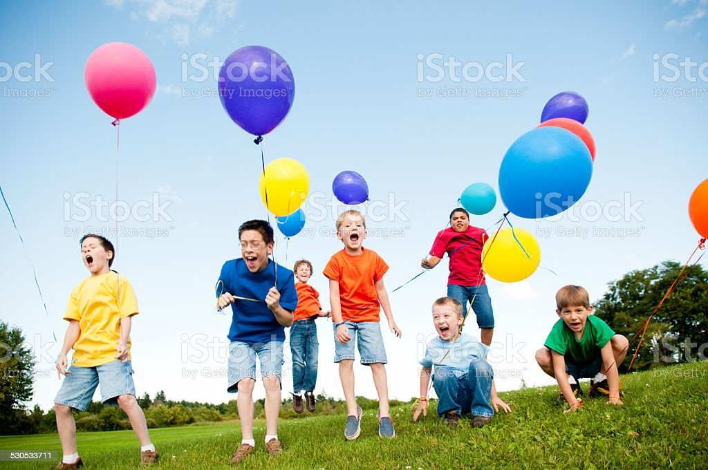 Group of Excited Boys Jumping and Yelling with Balloons Outside stock photo